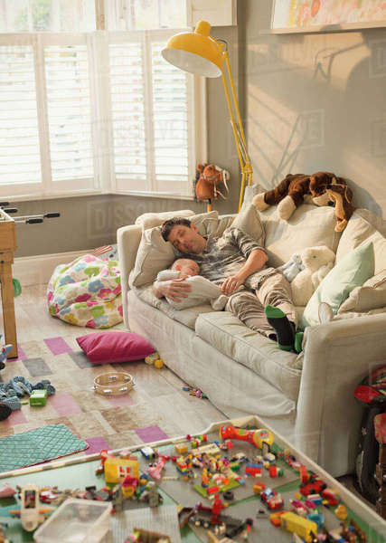 Exhausted father and baby son sleeping on sofa in messy living room with toys Royalty-free stock photo