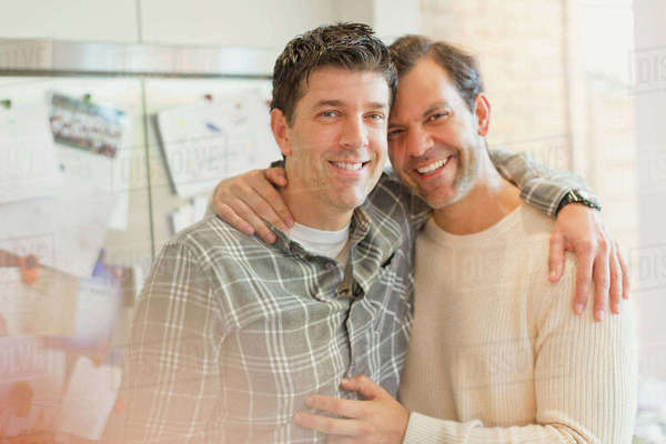 Portrait smiling, affectionate male gay couple hugging in kitchen Royalty-free stock photo