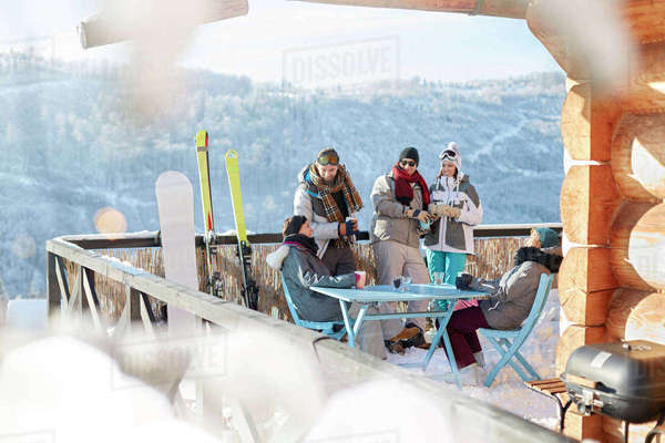 Skier and snowboarder couples hanging out on sunny cabin balcony apres-ski Royalty-free stock photo