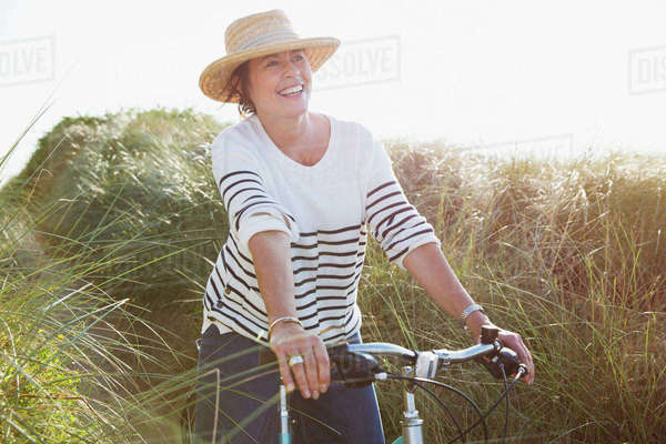 Smiling mature woman riding bicycle on sunny beach grass path Royalty-free stock photo