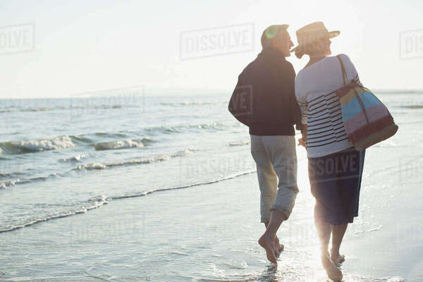 Barefoot mature couple walking on sunset beach Royalty-free stock photo