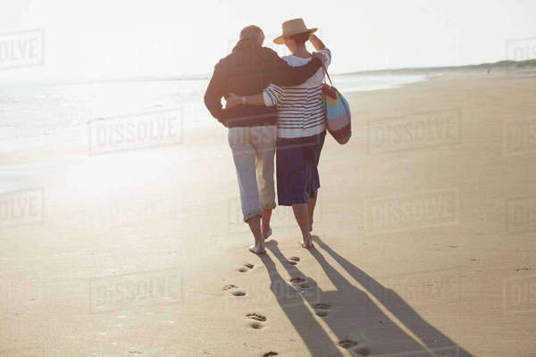 Mature couple hugging and walking on sunny beach Royalty-free stock photo