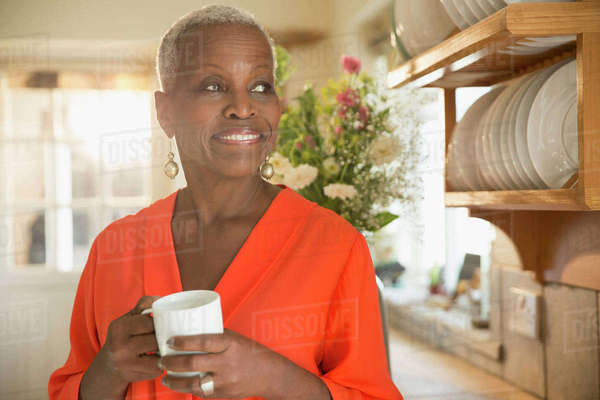 Smiling senior woman drinking coffee in kitchen Royalty-free stock photo