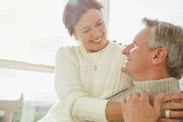 Affectionate mature couple hugging on sunny porch Royalty-free stock photo