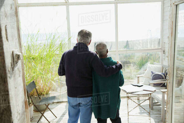 Affectionate senior couple enjoying beach view on sun porch Royalty-free stock photo