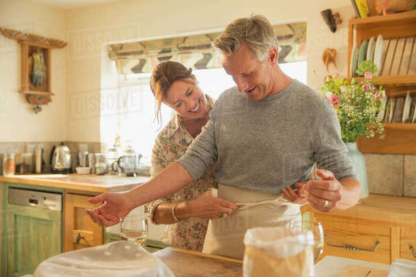 Playful mature couple baking, putting on apron in kitchen Royalty-free stock photo