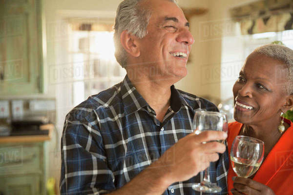 Laughing senior couple drinking white wine Royalty-free stock photo