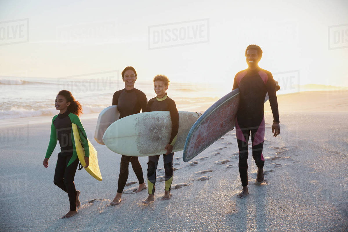 01c3133bb7 Family surfers carrying surfboards on summer sunset beach - Stock ...