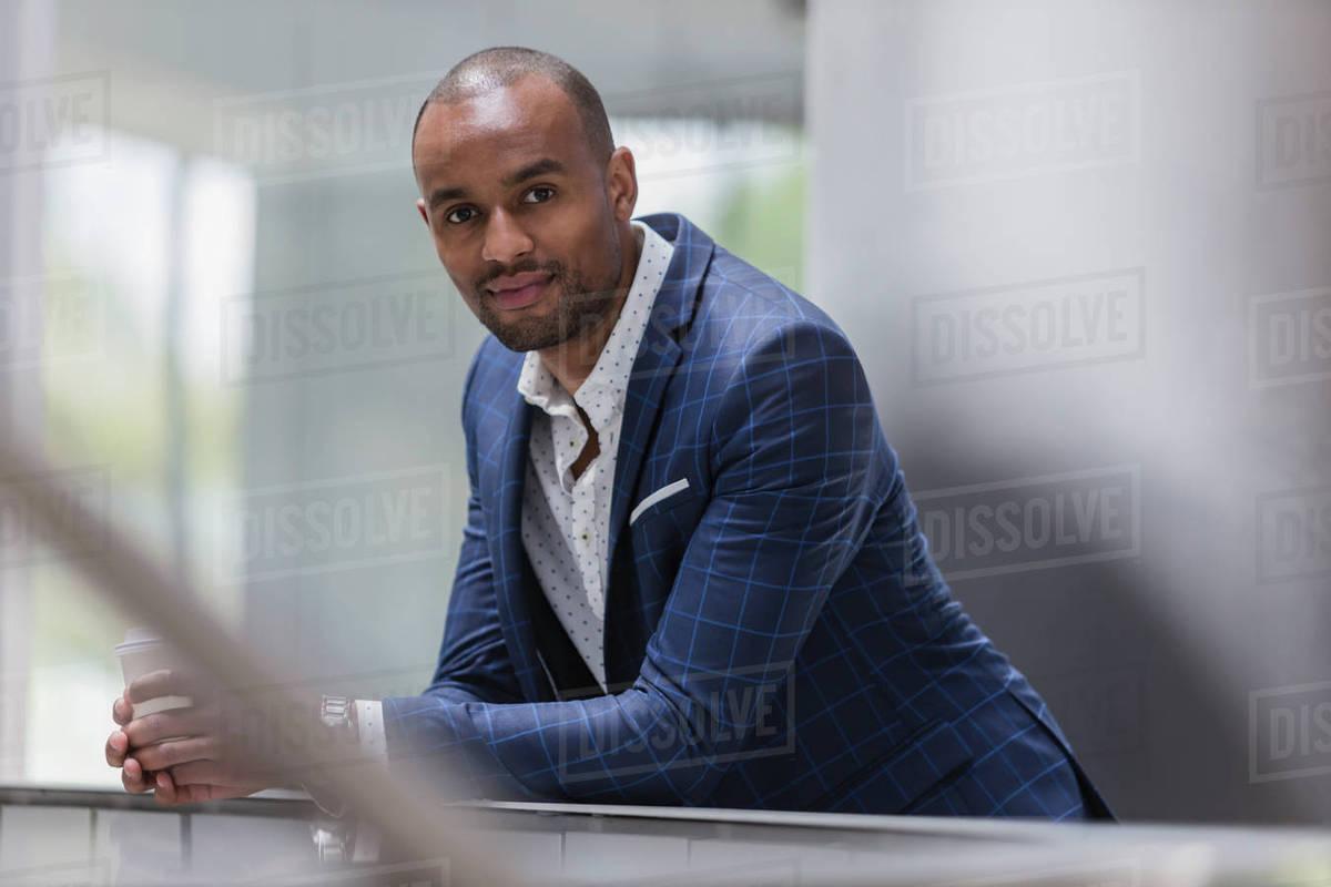 portrait confident businessman leaning on railing stock photo