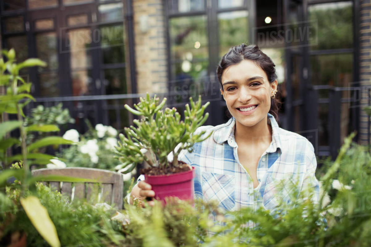 Portrait Smiling Young Woman Gardening With Potted Plants On Patio