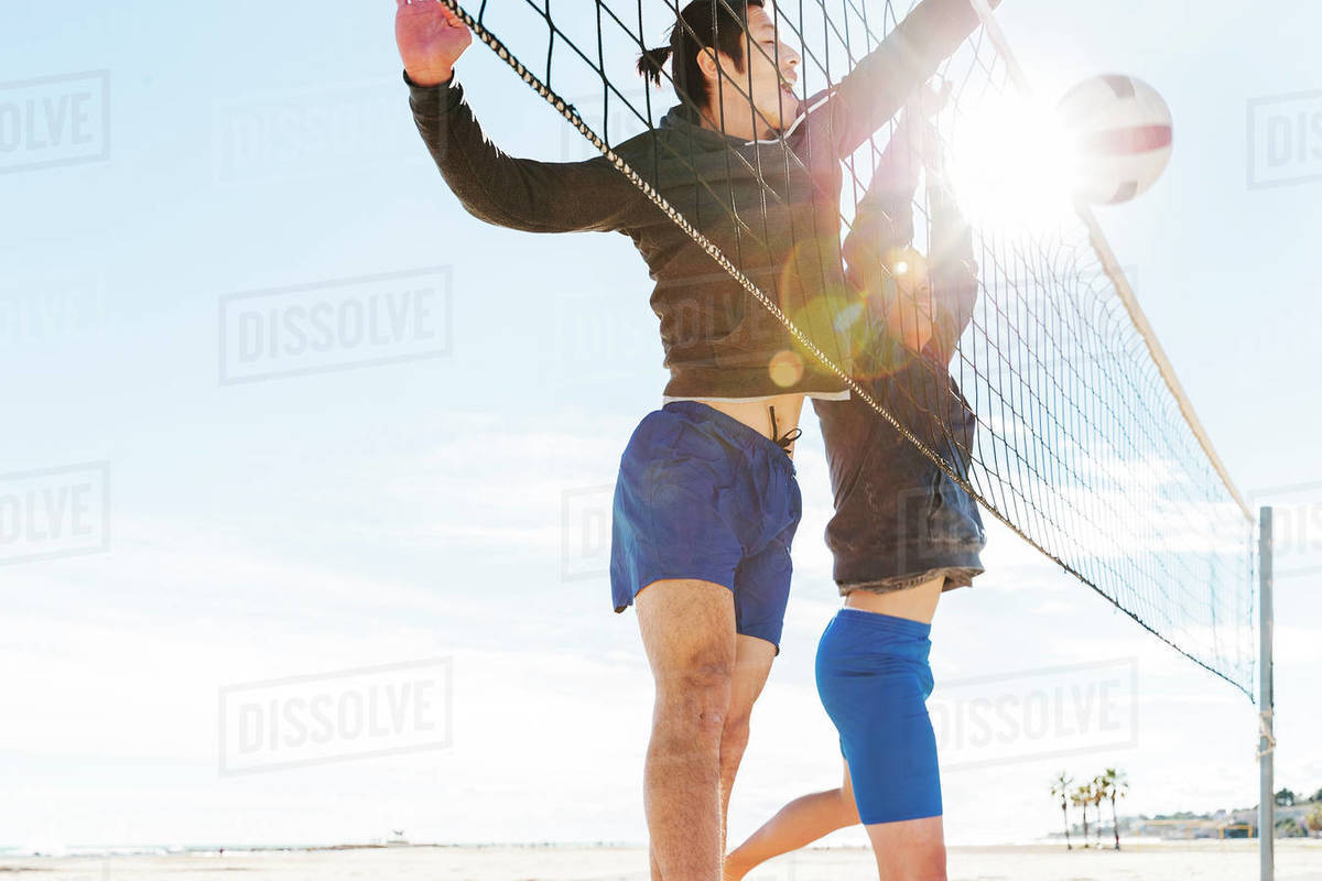 Men playing beach volleyball on sunny beach Royalty-free stock photo