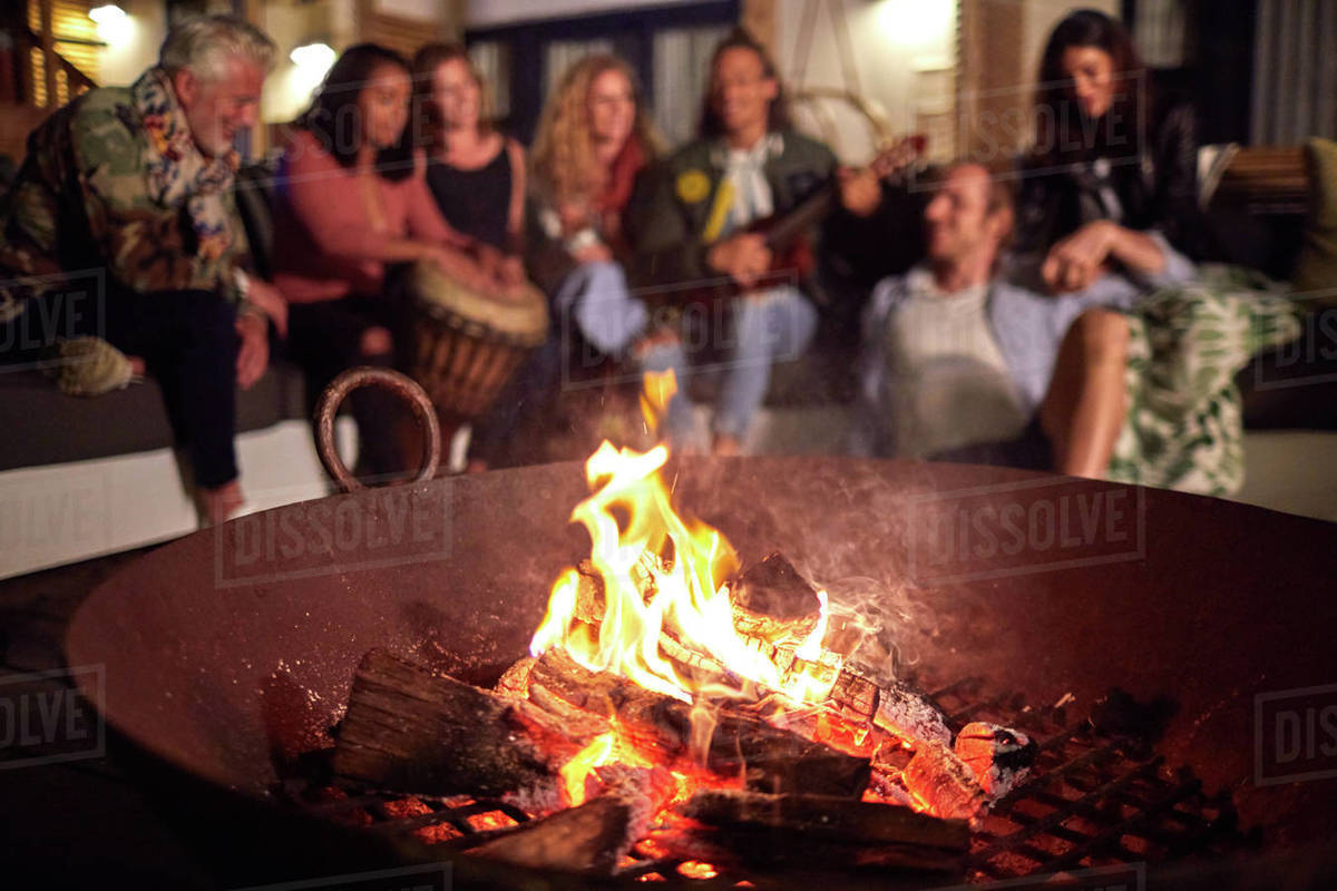 Friends hanging out, playing music on patio next to fire pit Royalty-free stock photo