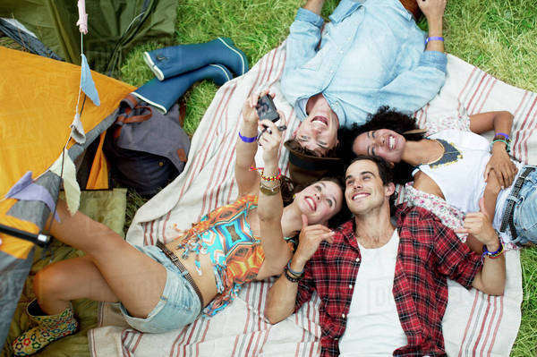 Friends taking self-portrait on blanket outside tent at music festival Royalty-free stock photo