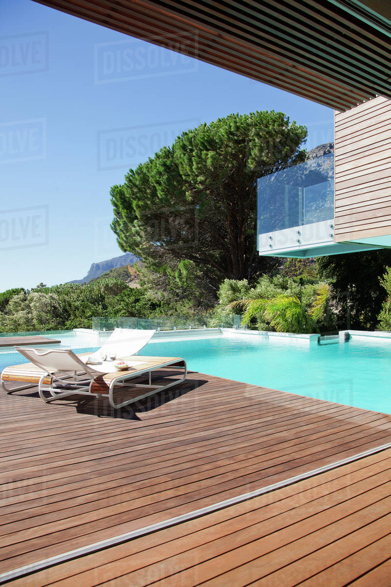 Luxury swimming pool and lounge chairs on deck - Stock Photo - Dissolve