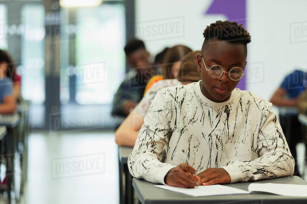 Focused high school boy student taking exam at desk in classroom Royalty-free stock photo
