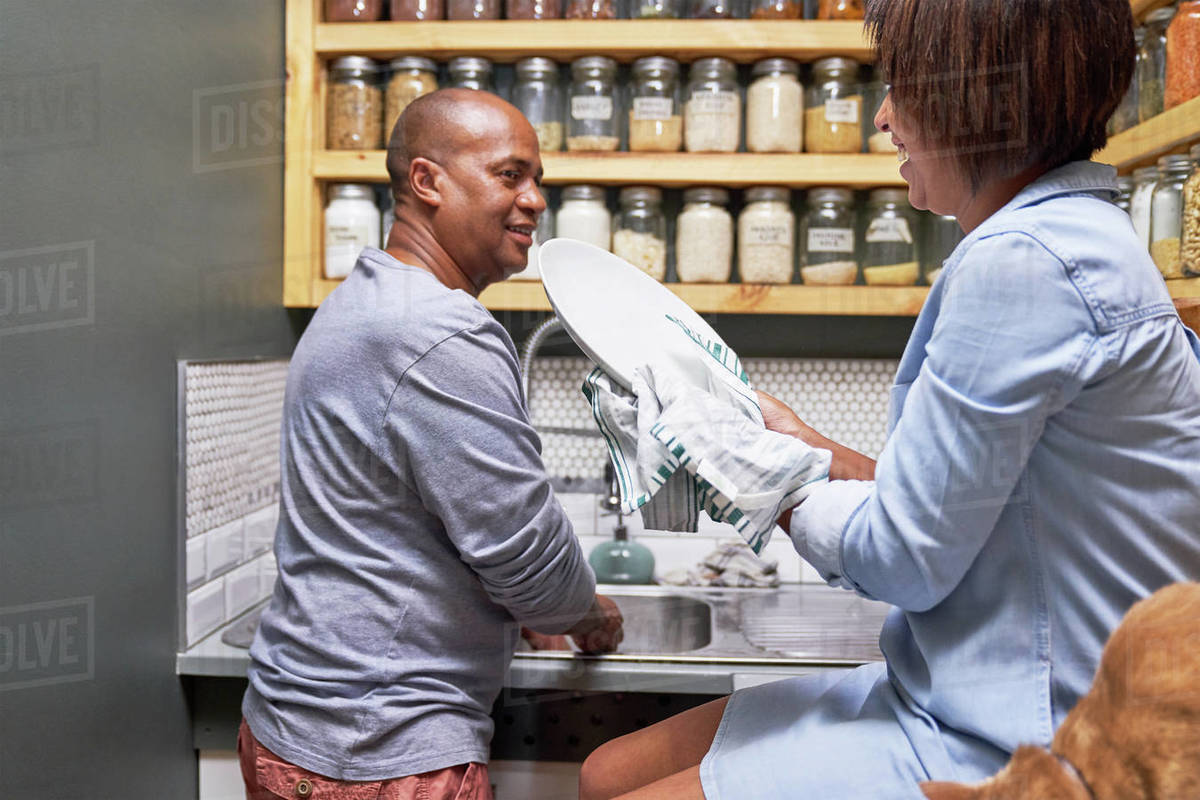 Couple talking and doing dishes in kitchen Royalty-free stock photo