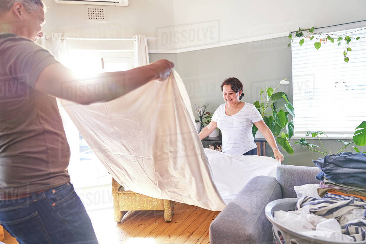 Smiling mature couple folding sheets in sunny living room Royalty-free stock photo