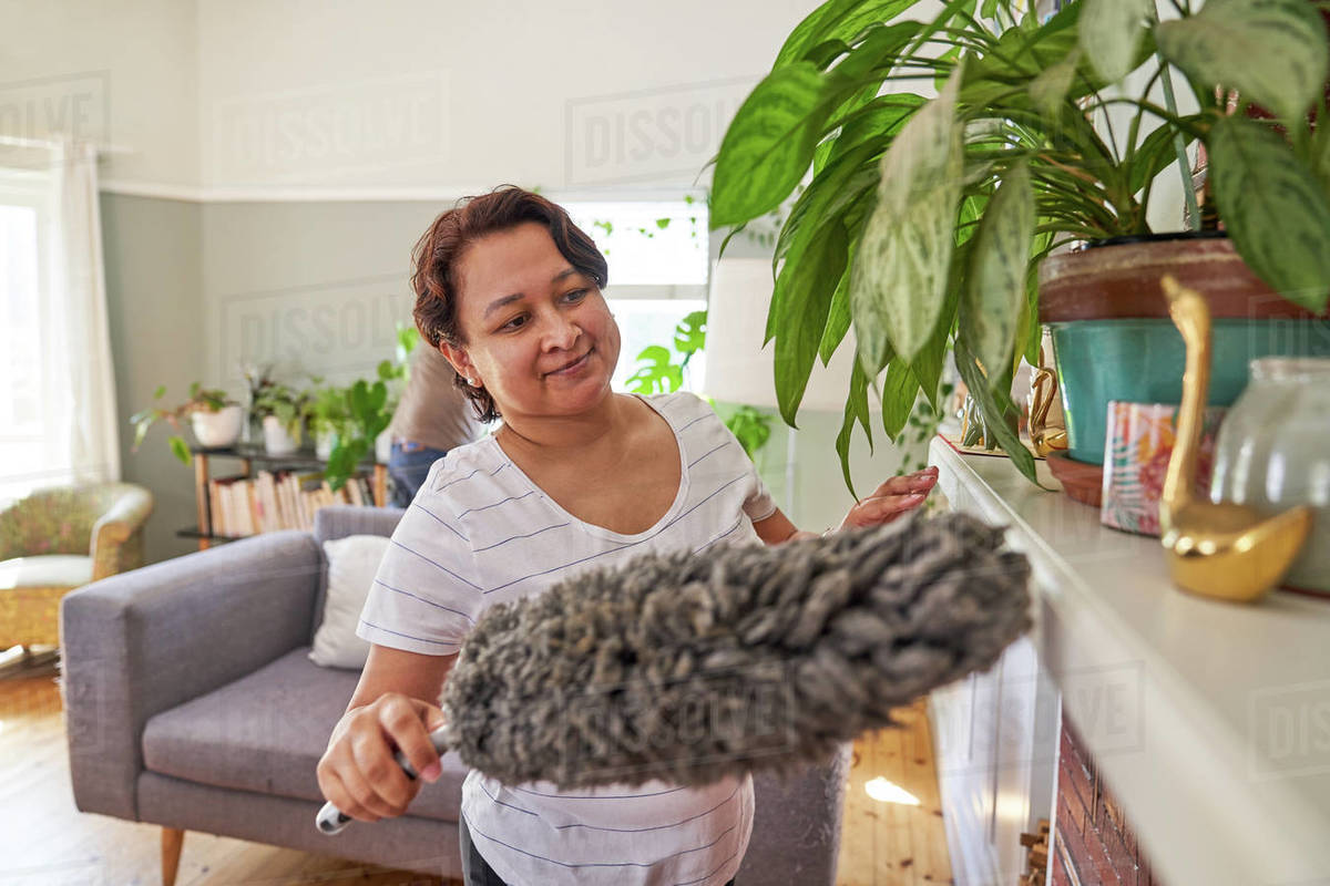 Mature woman with duster dusting living room Royalty-free stock photo