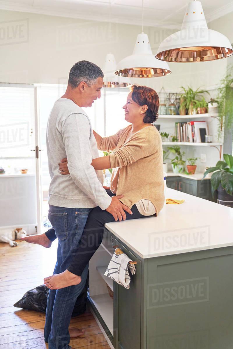 Happy affectionate couple talking on kitchen island Royalty-free stock photo