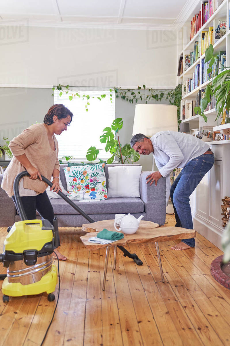 Mature couple vacuuming and cleaning living room Royalty-free stock photo