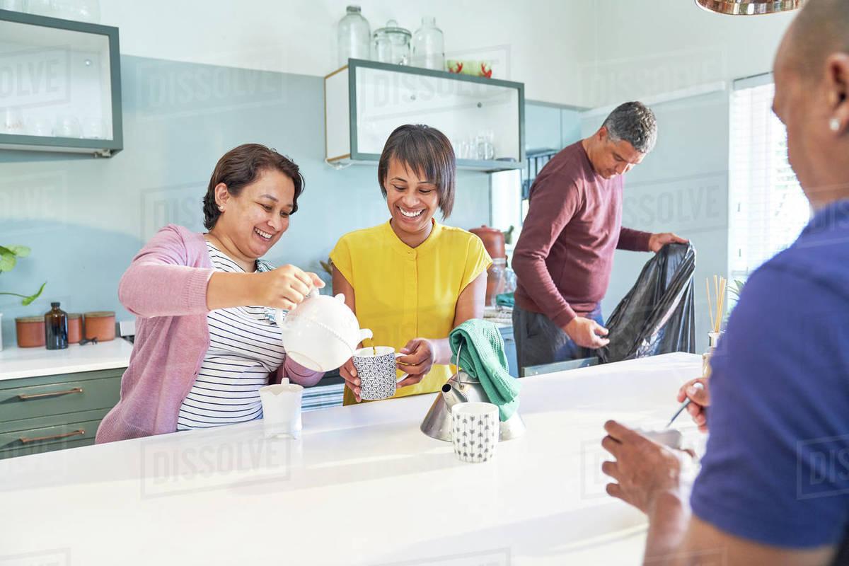 Happy women friends enjoying tea in kitchen Royalty-free stock photo