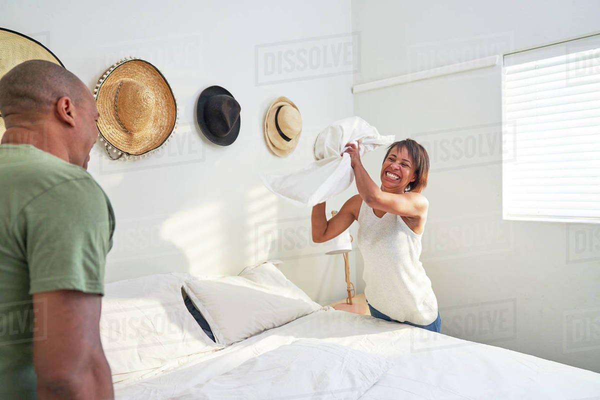 Playful couple making bed in bedroom Royalty-free stock photo