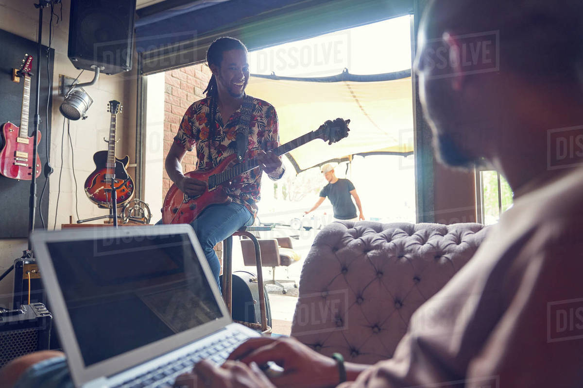 Musicians with laptop and electric guitar in recording studio Royalty-free stock photo