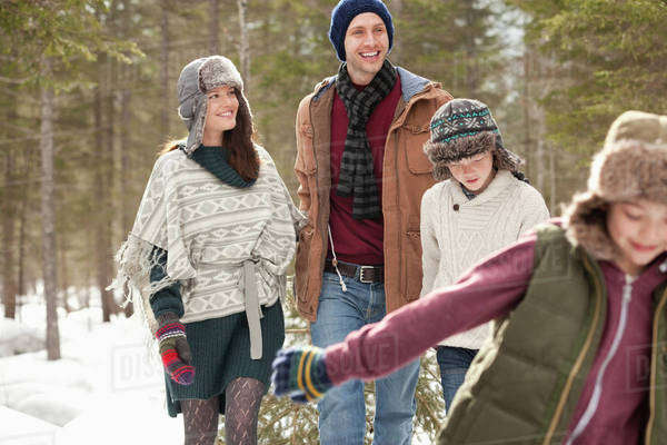 Happy family pulling Christmas tree in snow Royalty-free stock photo