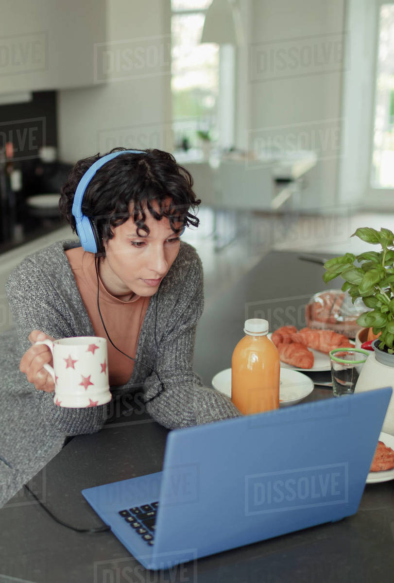 Woman with headphones working from home at laptop in morning kitchen Royalty-free stock photo