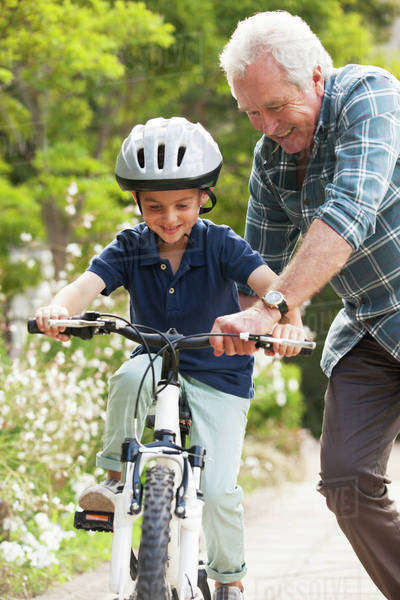 Grandfather teaching grandson to ride bicycle Royalty-free stock photo