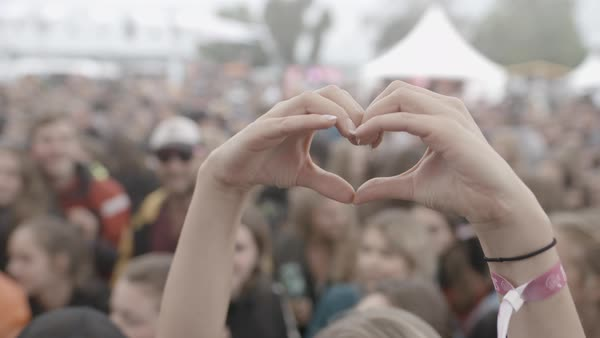 Hand-held shot of a woman forming a heart shape with her hands Royalty-free stock video