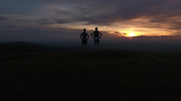 Wide shot of two men watching the sunset Royalty-free stock video