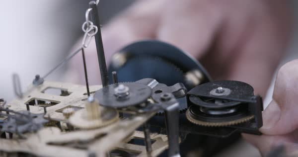 Close-up of a hand spinning cogs of a traditional German cuckoo clock Royalty-free stock video