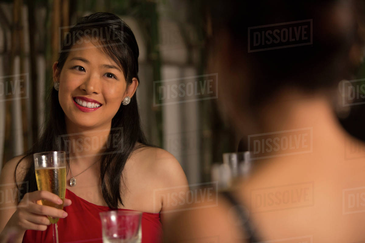 Two women in formal dress at dining table with champagne - Stock ... 893427abc