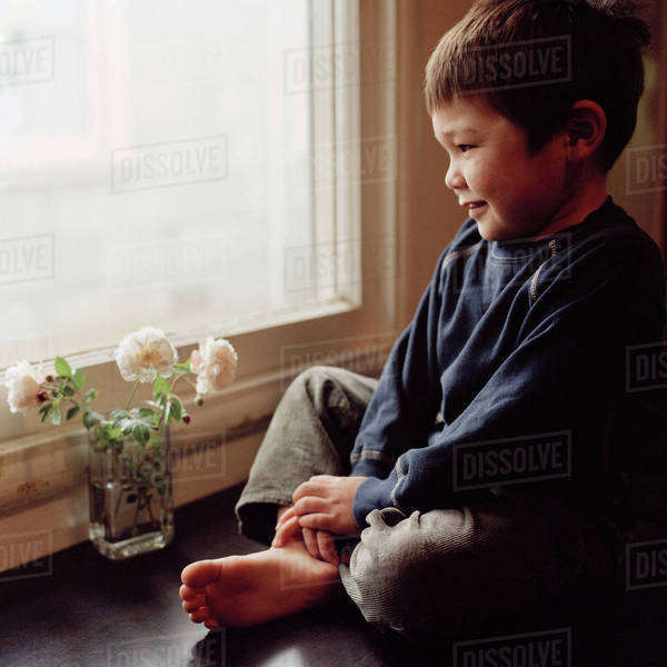 A smiling boy staring out window Royalty-free stock photo