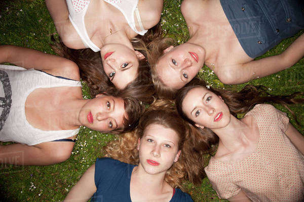 Five female friends lying in the grass in a circle looking sensually at the camera Royalty-free stock photo