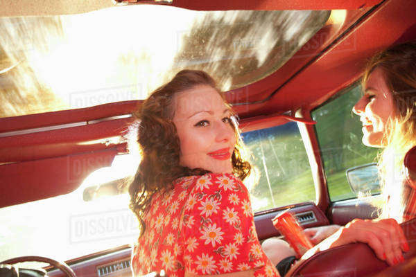 Two rockabilly women having fun in the front seat of a vintage car Royalty-free stock photo