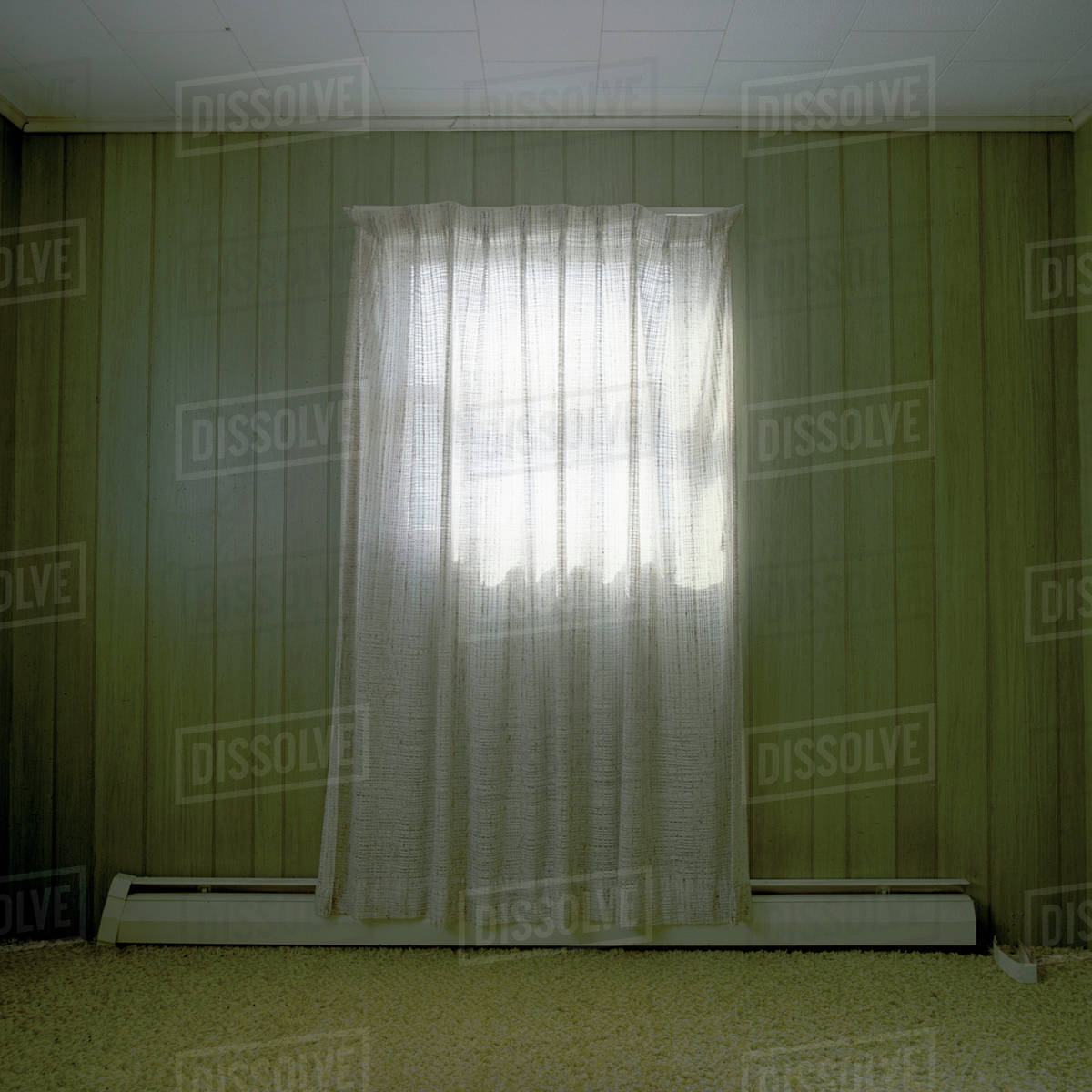 A Room Bare Of Furniture With A Single Curtained Window