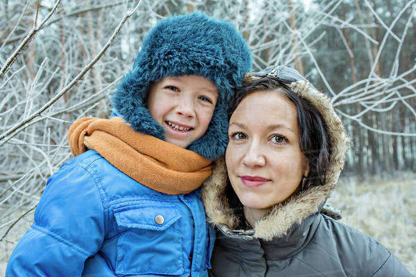 A cheerful mother and son in warm clothing outdoors in winter Royalty-free stock photo