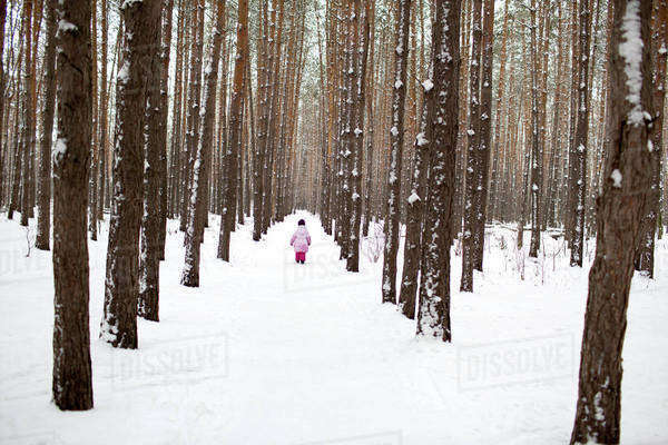 A young girl walking down a snow packed path in the forest Royalty-free stock photo