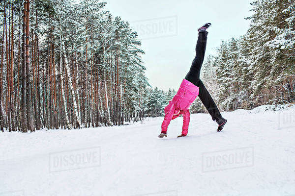 A woman doing a cartwheel in the snow Royalty-free stock photo