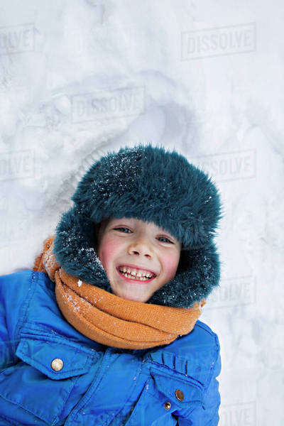 A young cheerful boy wearing warm clothing outdoors lying in the snow Royalty-free stock photo