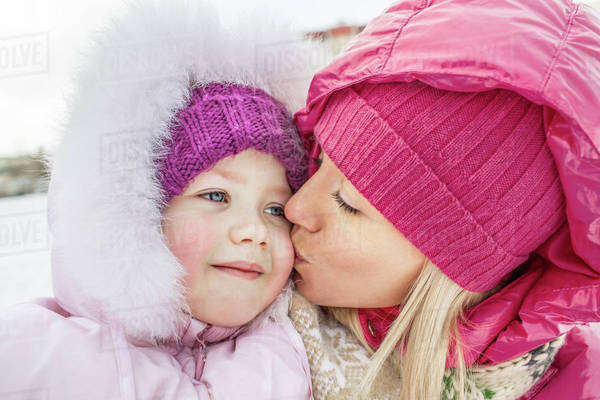 A mother kissing her daughter outdoors in winter Royalty-free stock photo