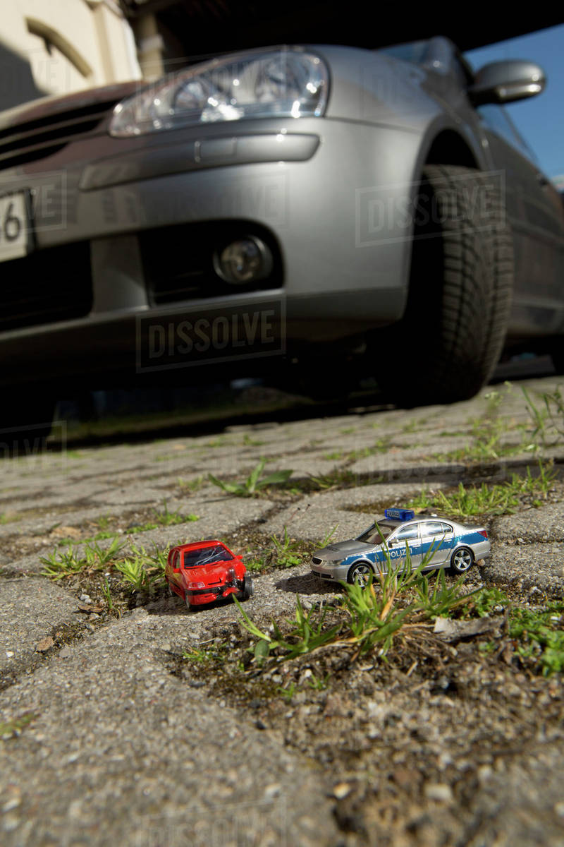 A Toy Car Crash With A Toy Police Car Real Car In Background