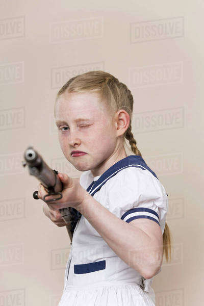 A tough girl wearing a sailor dress aiming a rifle at the camera Royalty-free stock photo