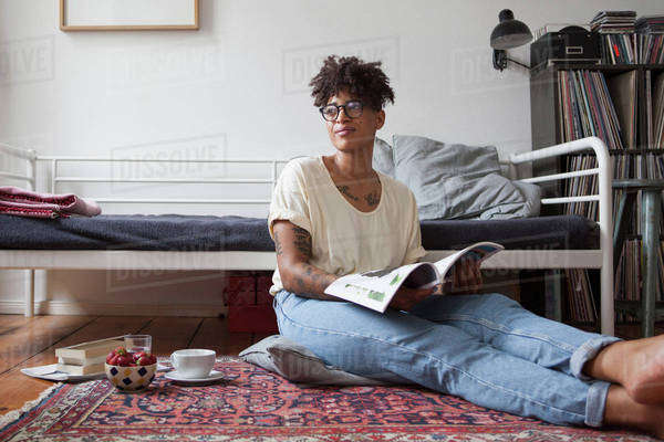 Young woman reading magazine in bedroom Royalty-free stock photo