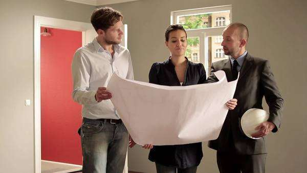 Tilt up, Tilt down, Medium shot of a young couple reviewing blueprints with an architect Royalty-free stock video