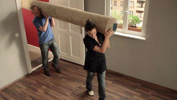 Medium shot, HA of three friends carrying a rolled up carpet into a house Royalty-free stock video