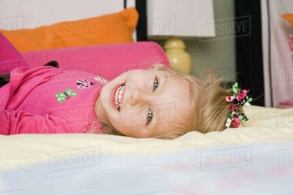 A young girl lying on a bed, portrait Royalty-free stock photo