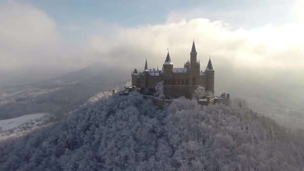 Panning shot of castle on top of mountain surrounded by snow covered trees, Burg Hohenzollern Royalty-free stock video